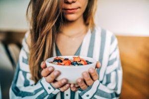 mujer sosteniendo un cuenco con frutos rojos para una piel más radiante