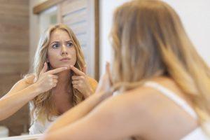 mujer preocupada por la aparicion de espinillas en su rostro